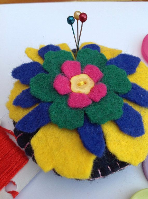 This is a hand sewn, circular shaped, felt pincushion with a flower motif and button detail. It can be used as a pincushion or a decoration to brighten up any home. This item measures approximately 8 cm x 8 cm and is made from high quality wool felt. Flower is cut using a Tim Holtz die, layering complementary colours of yellow, blue, green and pink to make the a beautiful flower motif, finished with a yellow button at the centre. The bottom layer is stitch on to the base cushion, while the…