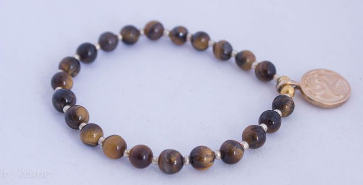 Tiger's eye bracelet with Om symbol  Approx 18cm diameter on strong stretchy thread. This little beauty is known for it's powers  of protection through stabilising and grounding, especially when travelling. It is thought to increase intuition, willpower and self confidence. AND all that aside... it is just so pretty https://www.etsy.com/listing/223966333/tigers-eye-bracelet-with-om-symbol?