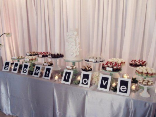 The dessert bar at a wedding- cake, mini desserts, and cake stands from Sweet and Saucy Shop