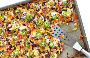 Seriously delicious nachos baked on a sheet pan with homemade tortilla chips, black beans, chicken and all the fixings. A family favorite for an easy meal or game day great!
