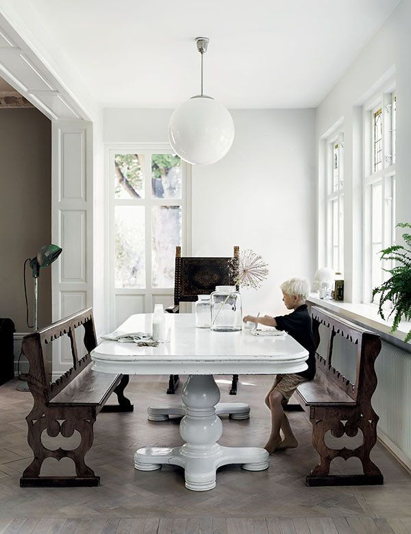 A dining room with a white dining table, ornate dark wood benches, globe light, and potted plant.