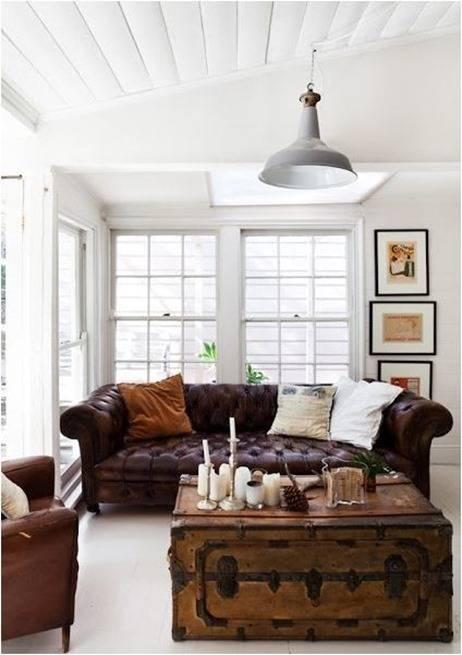 Sofá de cuero con cojines claros + marcos oscuros sobre blanco