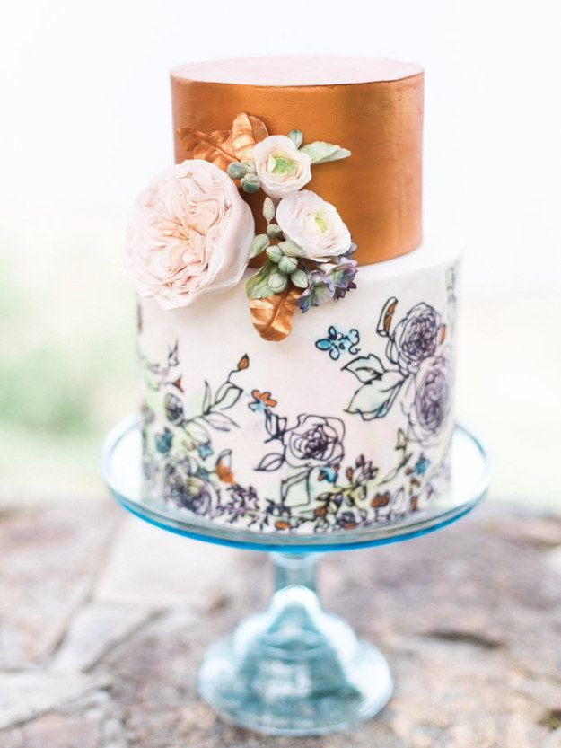 A wedding cake with painted blooms and a copper top.