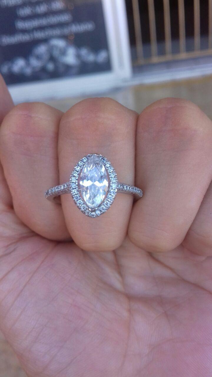 Hermoso anillo de plata FINA 9.25 con un simulante de diamante central en corte marquise de 8.5 x4mm sujetado por 2 uñas.Quien rodea a esta piedra es una base de 26 simulantes de diamante de 0.01 ctw, haciendo resaltar aun mas la piedra que protagoniza este anillo. Tiene una banda con un total de 20 circonias europeas a los laterales.  *Disponibles en todas las tallas  Garantía de por vida  Certificado de autenticidad  Empaque y caja de la marca Eva's  Envíos 100 % asegurados  *Somos…