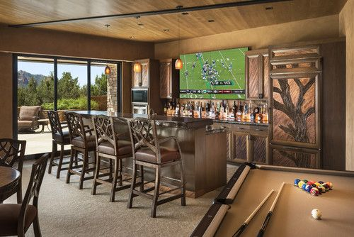 Large game room with mesquite bar top, swivel bar stools, quad TV, custom cabinets hand carved with bronze insets, game table, custom carpet, lighted liquor display, venetian plaster walls, custom furniture | Susan Hersker, ASID - Interior Designer of Arizona #interiordesign #homebar