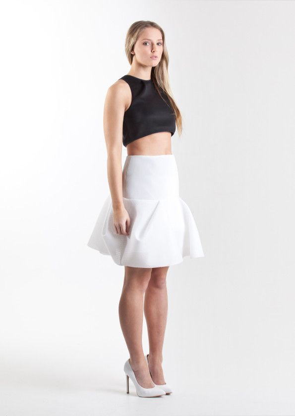 Leigh Duffy  WHITE REPERTOIRE SKIRT  The Repertoire Skirt is a sculpted peplum-style short skirt, shaped in a flirtatious silhouette and formed in neoprene mesh. The Repertoire Skirt is fully lined with a left side seam invisible zip. Model wears a size 8.  Available in black or white.   Designed and made in Melbourne, Victoria.   Shop now: www.thedresscollective.com