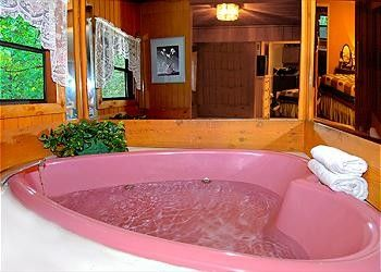 """Mountain Honey - Enjoy this cozy getaway with your """"honey"""" and stay in the mountains of Gatlinburg. Mountain Honey has a King size log bed and a pink heart shaped jacuzzi in the bedroom. Also for your enjoyment is a jetted bathtub and a rain shower head in the bathroom. Pet friendly.   #cabinrentals #romantic #smokymountains"""