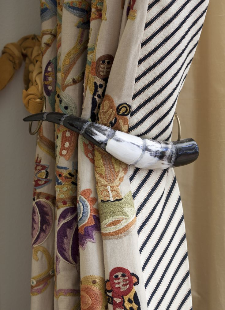 Drapery with black & white striped banding on lead edge and a faux animal horn for a tie back..