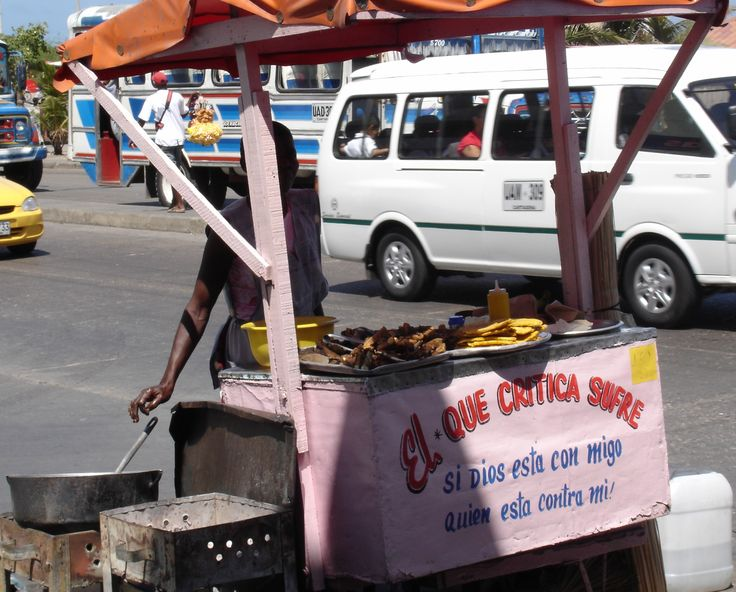 A food stall serving fried meat and plantain. The stall's name is 'He who criticises, sufers'