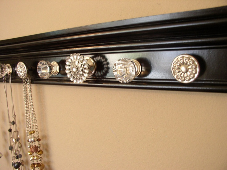 jewelry holder organizer featuring rhinestone center knob and total of 9 decorative  knobs on black wood background 26 inches long. $47.00, via Etsy.