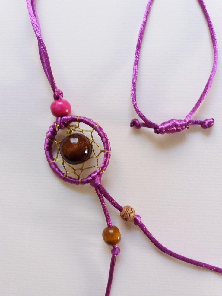 Collar atrapa sueños morado, hecho a mano,  adornado con diversas piedras en distintos tonos y texturas.