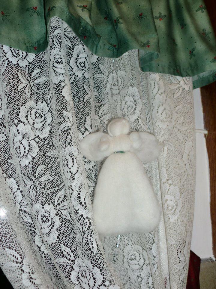 Grønnjulekappe over gardinene og engel med grønnt perlebelte.