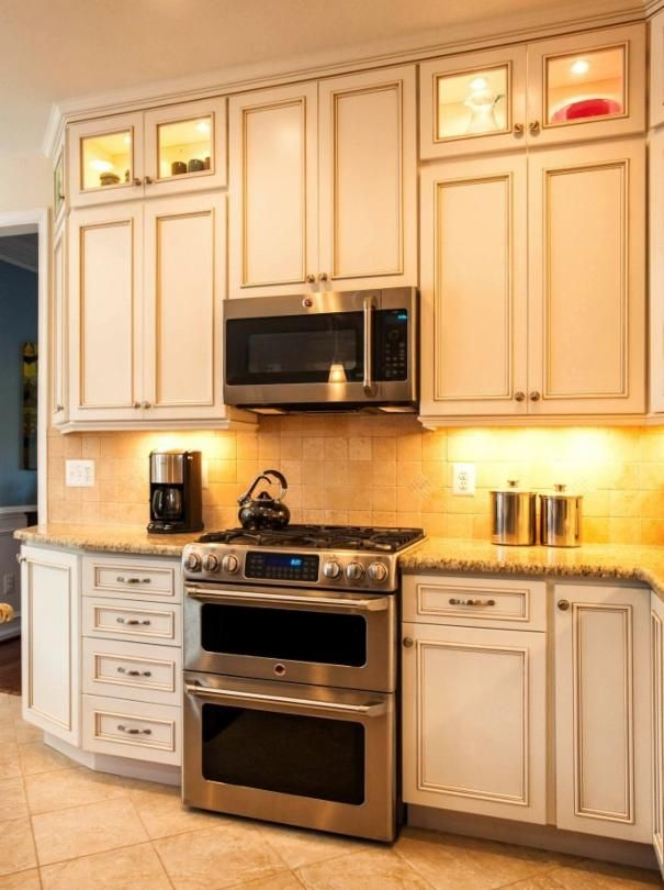 Photo of Beige Kitchen project in Fairfax, VA by Michael Nash Design Build Homes- upper cabinets and stove with microwave above