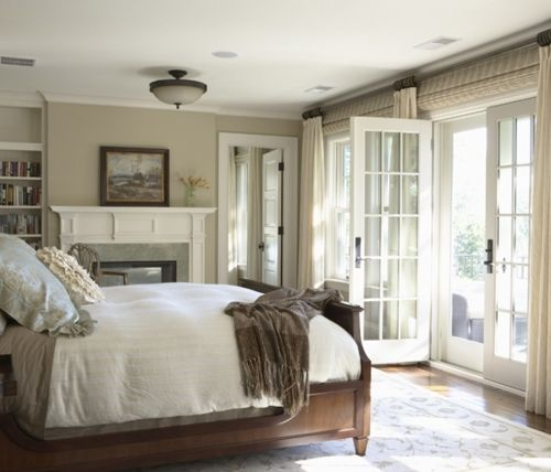 Beautiful neutral bedroom with tan walls, fireplace, wood bed, French doors, bamboo roman shades, ivory curtains and built-ins. http://www.decorpad.com/photo.htm?photoId=85688=13=1=curtains=photos