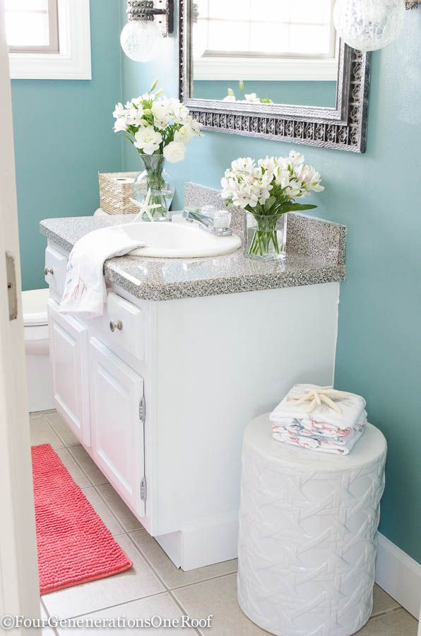 Gorgeous blue green powder room makeover {before & after) . I love how the blue paint color (drizzle by Sherwin-Williams) coordinates with the white and coral accessories.