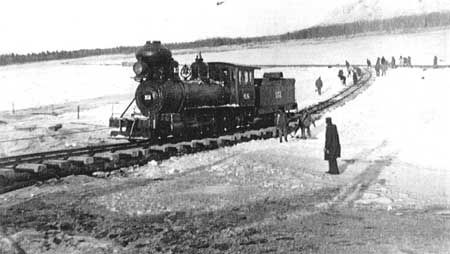 An Alaska Railroad steam locomotive crossing the Tanana River on the ice at Nenana just prior to completion of the railroad in 1923.