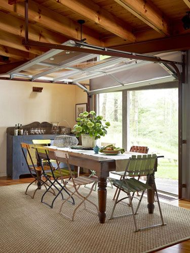 Commercial garage door used as a window wall in a dining area / Explore a Cozy and Rustic Cabin in Massachusetts