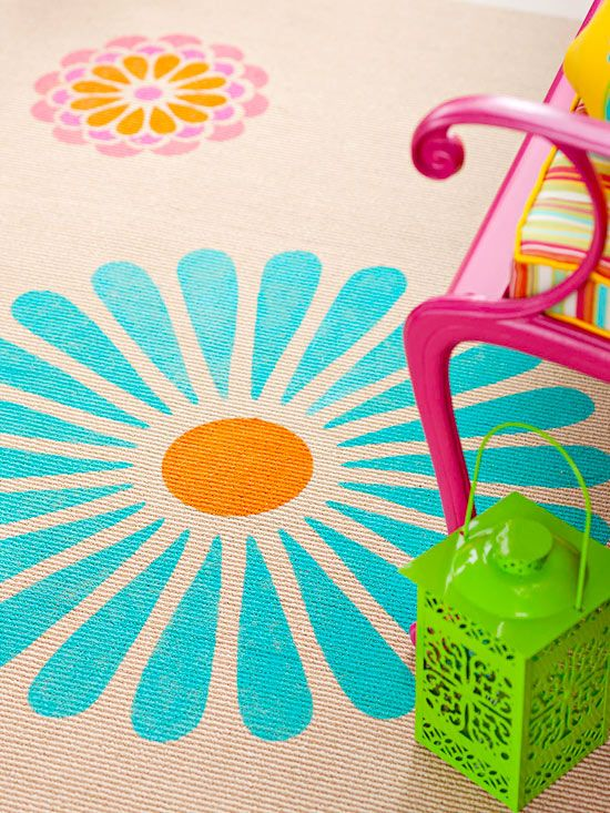 """Another great tip from BHG.com, used here for an outdoor space, but I would totally do this in a kid's room. A plain outdoor rug can be an inexpensive and sturdy springboard for a custom theme! """"An inexpensive outdoor area rug blooms thanks to an oversize floral stencil and some bright paint."""""""