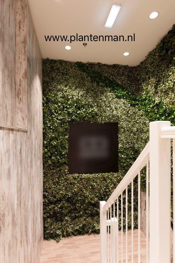 Groene wand met levensechte kunstplanten.