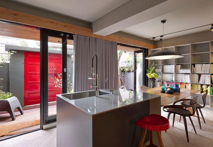 L'intera casa si affaccia, attraverso una serie di finestrature in sequenza, su un giardino privato con l'accesso in legno rosso