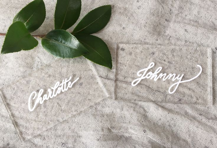 Acrylic place cards or escort cards beautifully written in elegant calligraphy.