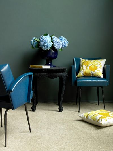 """That chalky, deep teal wall color is the perfect backdrop for the rich blues and pops of yellow in this room"" (green, dark teal is another color besides grey-blue for the walls )"
