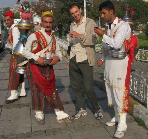 23 Fast, Easy Men's Halloween Costumes You Can Make at Home ~ These ideas for mens Halloween costumes will help you get dressed for the party faster than you get dressed for work. You don't have time to make an ornate costume, but you can still be creative with the stuff you have at home!  In the photo is Bruce, drinking tea with the locals in Turkey. How easy is this Halloween costume for men: white pants, a white man's dress shirt, a red vest, and a red sash.