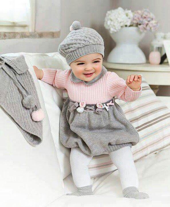 La bebe lleva una gorra gris, una camisa rosada, y una falda gris.