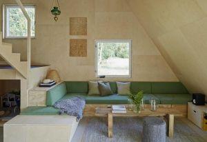 Il divano disegnato dall'architetto offre vani per lo storage e diventa tutt'uno con la scala che conduce alla zona notte della casa di vacanza svedese. I mobili sono in compensato