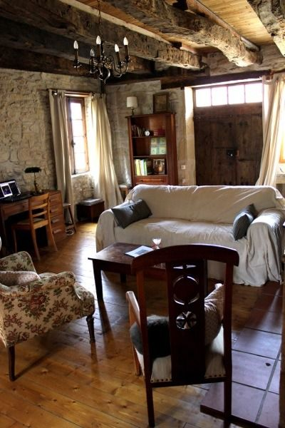 I like the mismatched furniture here. Family Uses 17th Century Tiny Stone Cottage in France for Escapades