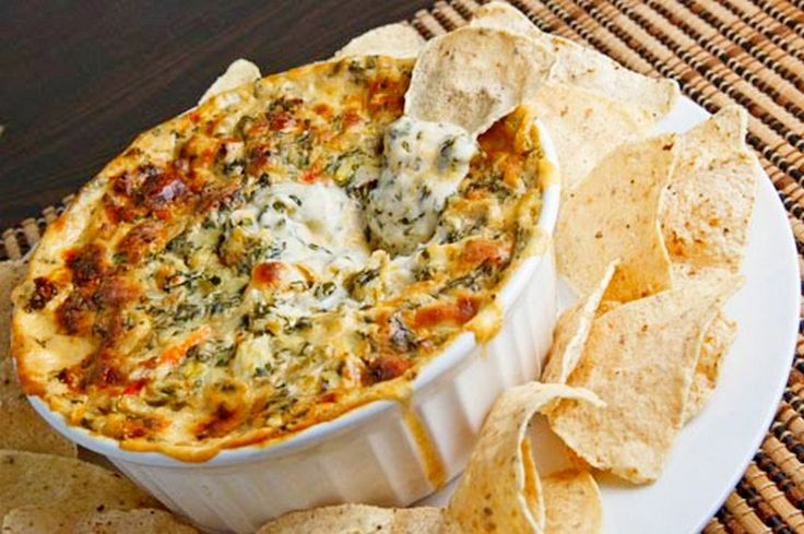Creamy Spinach Artichoke & Crab Dip, This is one of my favorite dips to bring to a party and its always a hit. It is delicious and creamy and has just the right amount of crab so it does not overpower the other ingredients. The tomato on top gives it a little extra burst of sweetness. Serve it with bread, chips, crackers, vegetables, etc.,