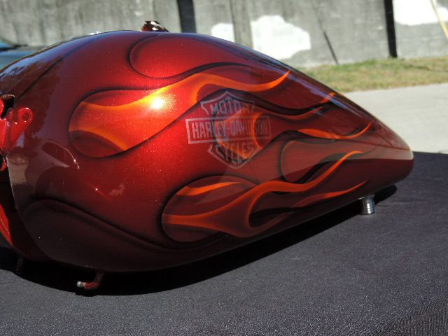 Candy red base, black ghost flames, candy tangerine ghost flames, ghost bar and shield.  Also airbrushed drop shadows. Beautiful paint job in the sun