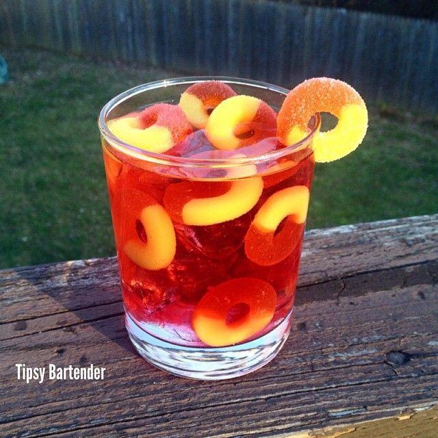 PRINCESS PEACH 1 oz. (30ml) Orange Vodka 1/2 oz. (15ml) Peach Schnapps 1/2 oz. (15ml) Banana Liqueur 3 oz. (90ml) Cranberry Juice or Peach Juice Splash of Sprite Peach Ring Gummies