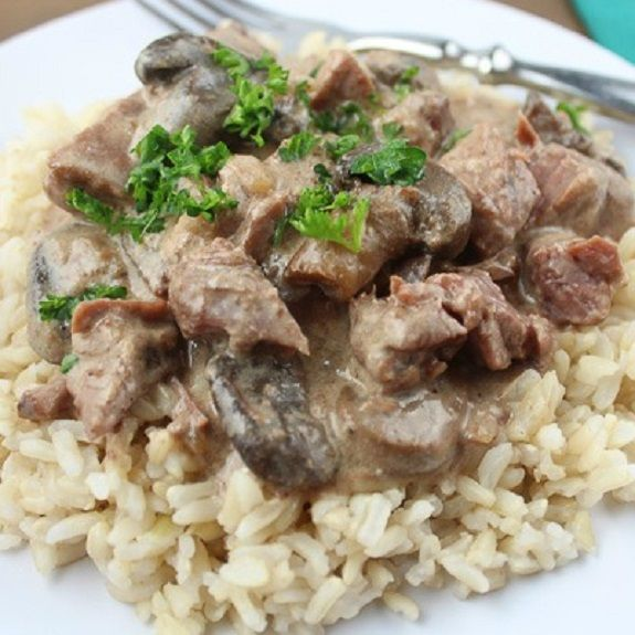 Creamy beef Stroganoff with rice.Famous beef Stroganoff with mushrooms and burgundy wine cooked in slow cooker.Horseradish adds a pleasant sharpness of flavor.