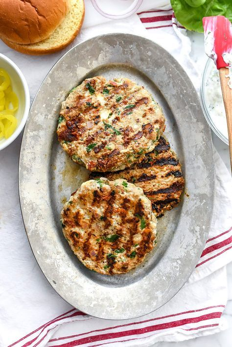 Greek Turkey Burgers with Tzatziki Sauce are packed with fresh spinach, sun-dried tomatoes, oregano and feta cheese for a healthy Mediterranean version for hamburger fans | http://foodiecrush.com