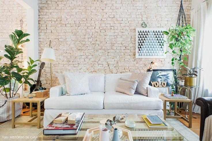 Sala de estar com clima nórdico tem parede de tijolinho, sofá branco e tons pastel.