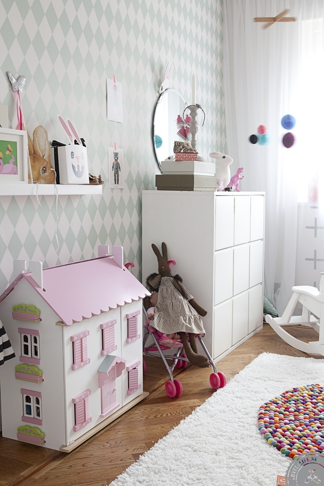 Kids room with Ferm Living's Harlequin Dusty Green wallpaper and Le Toy Van pink and white dollhouse.
