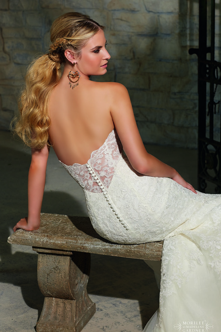 Floral lace overlays the mermaid silhouette of Mori Lee 2713 wedding dress, crowned with a strapless sweetheart neckline. Coated buttons march down the lace back toward the derriere. Tapered through the thighs, this lacy ensemble then transitions into a scalloped full-length skirt that extends with a sweep train.