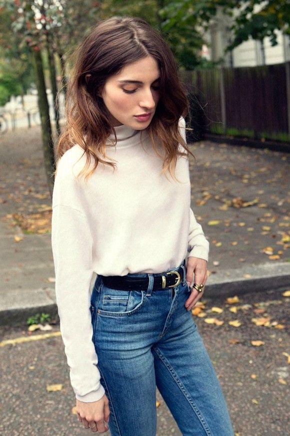 Un look simple et efficace : pull blanc, jean taille haute bleu, ceinture noire et bague dorée