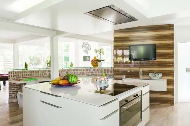 Der Materialmix aus hochglanzlackiertem Holz, weißem Glattlack und der dünnen Arbeitsplatte verleiht der Küche den rustikal-modernen Großstadt-Flair eines New-Yorker Lofts.