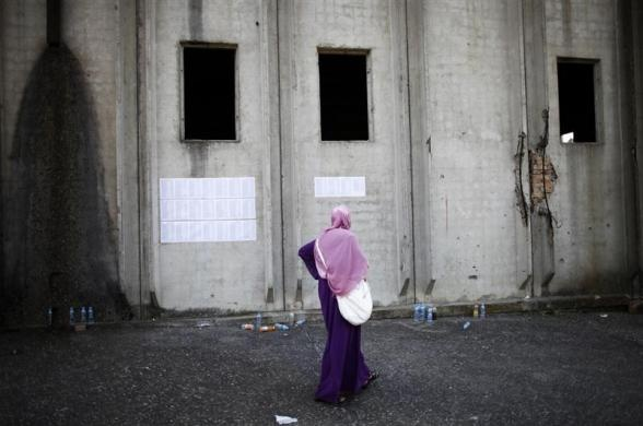 A Bosnian Muslim woman looks at papers with names of people who were killed near coffins prepared for a mass burial at the Memorial Center in Potocari, near Srebrenica July 9, 2012. The bodies of 520 recently identified victims of the Srebrenica massacre will be buried on July 11, the anniversary of the massacre when Bosnian Serb forces commanded by Ratko Mladic slaughtered 8,000 Muslim men and boys and buried them in mass graves, in Europe's worst massacre since World War Two. REUTERS-Dado…