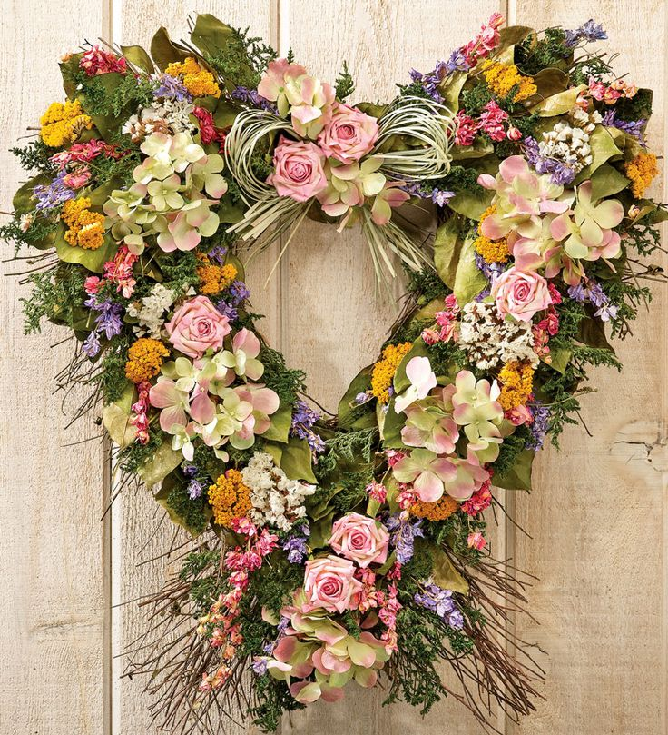 Garden Heart Wreath Like a floral love letter, this heart-shaped wreath is full of romantic beauty. Designed by floral artisans in Mexico with natural salal leaves, green caspia, pink larkspur, lavender larkspur, white sinuate, yarrow, natural grass and is delightfully accented with large fuchsia tipped handmade parchment roses and light pink and green lavender hydrangea.