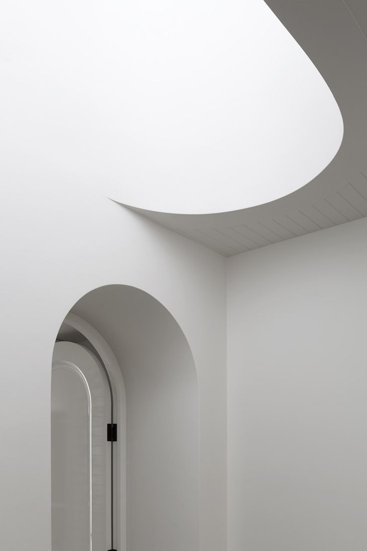 B.E Architecture arched door meets smooth curved stair cutout at Hopetoun Road Residence