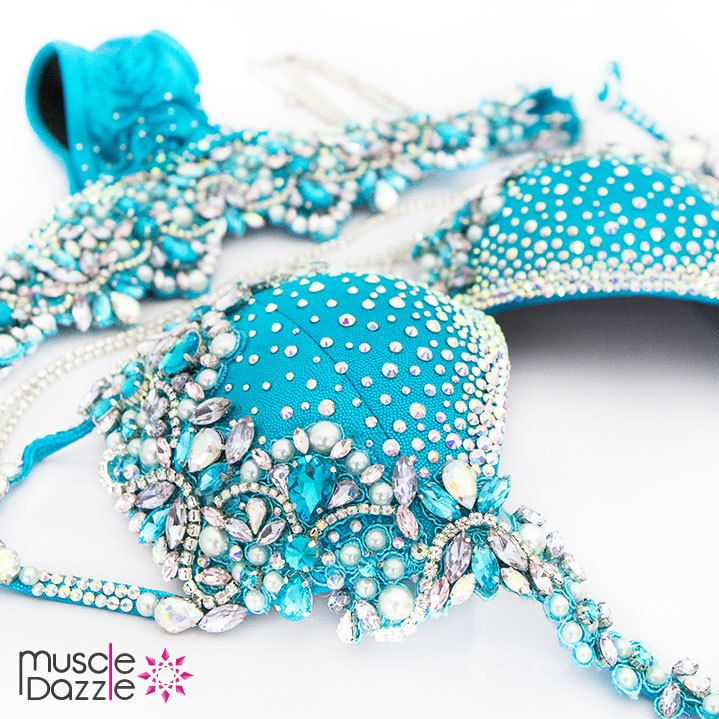 Heads will turn... jaws will drop! This blue bikini competition suit is a beautifully styled design of clear and blue rhinestones, larger crystals, pearls, chain and lace. Blue WBFF Bikini Competition Suit DV025. #muscledazzle #competitionbikini #crystalbikini #bikinicompetition #wbff #wbffbikini #wbffbikinidiva #wbffdiva #wbffbikinipro #wbffpro #bikinidiva #divabikini #fitnessdiva #couturebikini #wbffbikinis #couturebikinis #bikinicompetitors #fitnessbikini #compbikini