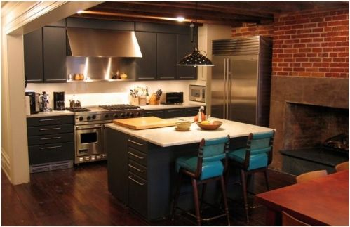 Julianne Moore's West Village Townhouse- Brick wall, hardwood floor, gray cabinets, wood beam/timber ceiling