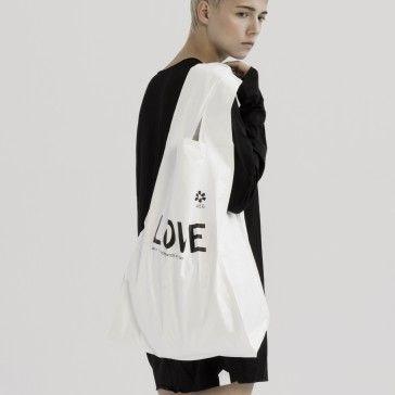 Średniej wielkości tyvekowa torba mająca formę zwykłej plastikowej reklamówki jest uszyta z dwóch warstw tyveku.  Wewnątrz torby wszyte są dwie kieszenie.   Na zewnątrz czarny nadruk: LOVE | HOPE | FAITH | DESTINY