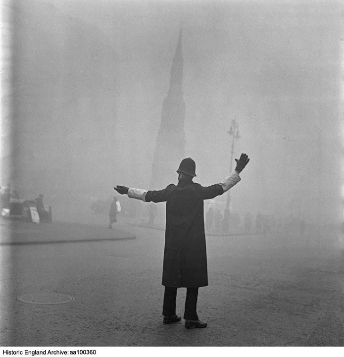 AA100360 A City of London traffic policeman outside the Charing Cross Hotel on the Strand, using outstretched arms to control vehicles, with the Queen Eleanor Memorial Cross silhouetted through fog in the background. Strand, Greater London, WC2     Date1946 - 1959 Photographer: John Gay