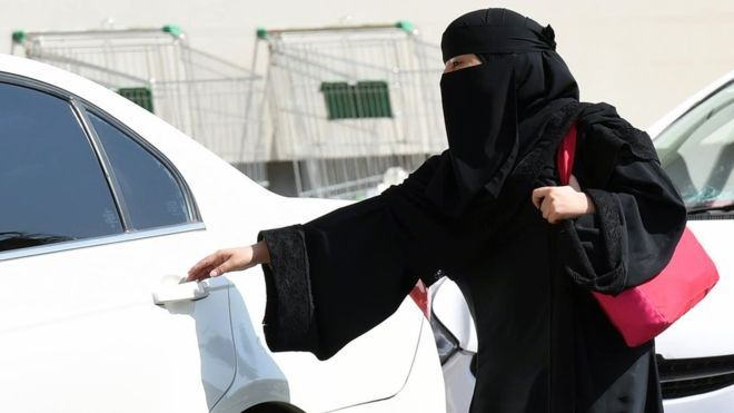 A Saudi woman wearing a Niqab gets into a taxi at a mall in Riyadh as a grassroots campaign planned to call for an end to the driving ban for women in Saudi Arabia on October 26, 2014
