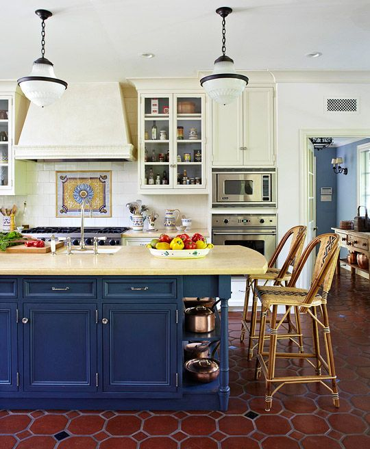 Blue and White Kitchen  White walls and white painted cabinets recede against the rich navy blue painted surface of a kitchen island topped with creamy yellow marble. An 18th-century Portuguese tile mural installed above the range draws the eye, while a terra-cotta tile floor peppered with blue diamond-shaped tiles defines the space.