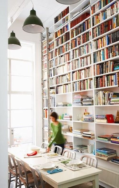 Floor to ceiling bookcases offer plenty of space to showcase a vast collection of books. A ladder gives access to books placed high on the bookcase.